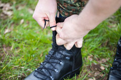 German soldier laces his boots on grass Royalty Free Stock Photos