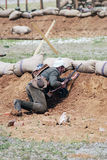 German soldier-reenactor hides behind the sand hill Stock Image