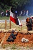 German soldiers-reenactors and old German flag waving Royalty Free Stock Photography