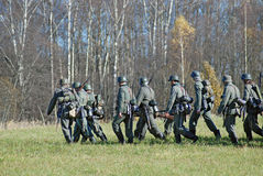 German soldiers-reenactors walk on green grass Stock Photo