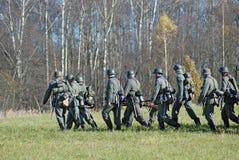 German soldiers-reenactors walk on green grass Stock Photo