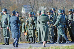 German soldiers-reenactors walk on green grass Stock Image