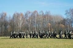 German soldiers-reenactors walk with guns Stock Photo