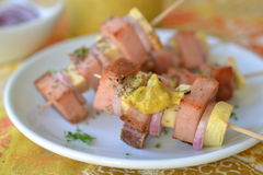 German specialty meat skewers. German leberkaese on skewers with apples and onions served with a mustard sauce Stock Photography