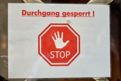 German stop sign, no passage. German sign on a glass door with the words for - passage closed - and a red stop icon stock photo