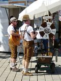German street musicians in traditional dress. German street musicians playing guitar and accordian wearing traditional brown leather shorts and braces on a sunny Royalty Free Stock Image