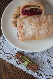 German strudel with cherry. Sweet cherry strudel of puff pastry; two slices on plate royalty free stock photo