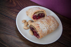 German strudel with cherry. Sweet cherry strudel of puff pastry; two slices on plate stock photo