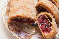 German strudel with cherry. Sweet cherry strudel of puff pastry; two slices on plate stock photography