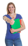 German student in a blue shirt showing thumb up Royalty Free Stock Images