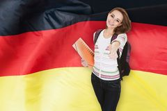 German student gesturing thumb up. Young German Female Student Gesturing Thumb Up In Front Of Germany Flag stock images