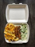German takeaway food schnitzel fries broccoli. German takeaway food: schnitzel breaded escalope with french fries and broccoli cheese sauce in polystyrene Stock Images