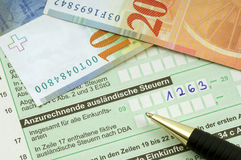 German tax. Form waiting to be completed, here with Swiss Francs for declaring income from abroad Royalty Free Stock Photography