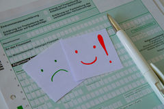 German tax declaration. A blank form for the German tax declaration with a pen and two smiles: a happy and unhappy one Stock Image