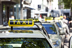 German taxi cabs waiting in line. Focus on sign on first car Stock Images