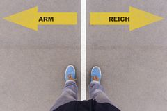 German text Arm and Reich poor and rich on asphalt ground. Arm and Reich German for poor and rich text on asphalt ground, feet and shoes on floor, personal stock photography