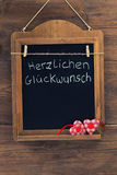 German text Herzlichen Glueckwunsch means Best Wishes written with chalk on aged blackboard with textile hearts hanging on wooden Stock Photos