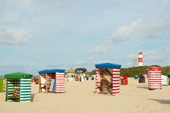 German wadden island Borkum. Beach of German wadden island with typical striped chair and lighthouse royalty free stock images