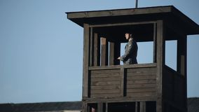 A young German guardian with a rifle is standing in a watchtower of a death camp and looking around. WW2 reenactment. A German watchman is guarding a stock video footage