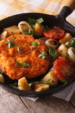 German Weiner schnitzel with fried vegetables in a pan closeup. Royalty Free Stock Image
