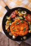 German Weiner schnitzel with vegetables in a pan closeup. Vertic Royalty Free Stock Image