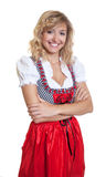 German woman with crossed arms in a traditional bavarian dirndl. On an isolated white background for cut out stock photo