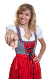 German woman in a traditional bavarian dirndl pointing at camera Royalty Free Stock Photo