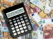 Free German Word GRUNDEINKOMMEN Basic Income Written On Display Of Pocket Calculator Against Cash Money On Table Royalty Free Stock Photo - 139722325