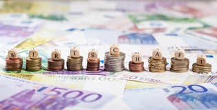 German word Wirtschaft on coin stacks, cash background. Cube letters building the term Wirtschaft in German. Shallow depth of field, focus on coin stacks and Stock Photos