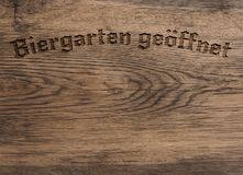 German words beer garden open on wood. Old used oak plank using a background, wooden texture with the German words beer garden or pub garden open stock images