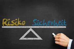 German words. `Risiko Sicherheit` risk security on blackboard as decision concept stock image