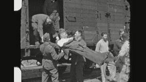 German Wounded Soldier Train Transport. UKRAINE, DNIPRO, SPRING 1942. Two Shot Sequence Of German Paramedics Carrying A Wounded Soldier Into A Hospital Train stock video footage