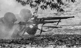 German WWII soldiers. German soldiers with rifles from Second World War period. Company firing on the front line in the gunpowder smoke. Historical military stock photography