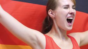 German Young Woman Celebrates holding the Flag of Germany in Slow Motion. High quality stock image