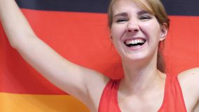 German Young Woman Celebrating while holding the Flag of Germany in Slow Motion. High quality stock photo