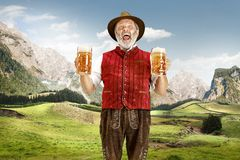 Germany, Bavaria, Upper Bavaria, man with beer dressed in traditional Austrian or Bavarian costume. Germany, Bavaria. The senior happy singing man with beer stock photo