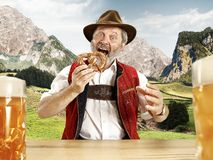 Germany, Bavaria, Upper Bavaria, man with beer dressed in traditional Austrian or Bavarian costume. Germany, Bavaria. The senior happy smiling man with beer stock photo