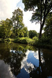 Germany,  Bavaria, sky, clouds and wood reflection on the surfac Stock Image