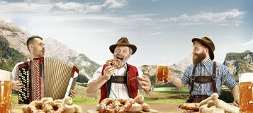 Germany, Bavaria, Upper Bavaria, men with beer dressed in traditional Austrian or Bavarian costume. Germany, Bavaria. The happy smiling singing men with beer stock photos