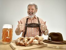 Germany, Bavaria, Upper Bavaria, man with beer dressed in traditional Austrian or Bavarian costume. Germany, Bavaria, Upper Bavaria. The senior happy smiling man stock photos