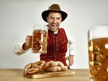 Germany, Bavaria, Upper Bavaria, man with beer dressed in traditional Austrian or Bavarian costume. Germany, Bavaria, Upper Bavaria. The young happy smiling man stock photos