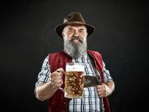 Germany, Bavaria, Upper Bavaria, man with beer dressed in in traditional Austrian or Bavarian costume. Germany, Bavaria, Upper Bavaria. The smiling man with beer royalty free stock photography