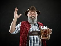 Germany, Bavaria, Upper Bavaria, man with beer dressed in in traditional Austrian or Bavarian costume. Germany, Bavaria, Upper Bavaria. The smiling man with beer stock image