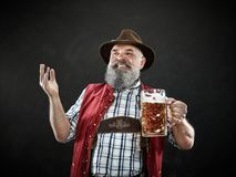 Germany, Bavaria, Upper Bavaria, man with beer dressed in in traditional Austrian or Bavarian costume. Germany, Bavaria, Upper Bavaria. The smiling man with beer stock images