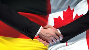 Germany and Canada handshake, international friendship relations flag background. Stock footage stock video