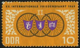 Postage stamp. GERMANY- CIRCA 1967: stamp printed by Germany, shows Bicyclists and doves. Arms Warsaw Berlin and Prague, circa 1967 stock image