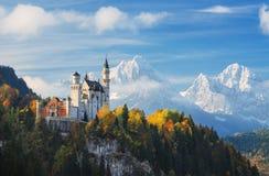germany Den berömda Neuschwanstein slotten i bakgrunden av snöig berg och träd med guling- och gräsplansidor Fotografering för Bildbyråer