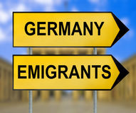 Germany and Emigrants traffic sign with blurred Berlin background Royalty Free Stock Photos