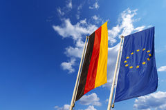 Germany and European Union Flags. Flags of Germany and European Union waving in the wind on blue sky with clouds Royalty Free Stock Photo