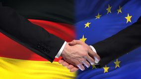 Germany and European Union handshake, international friendship, flag background. Stock footage stock footage